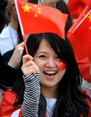 Китайська дівчина посміхається, тримаючи національний прапор